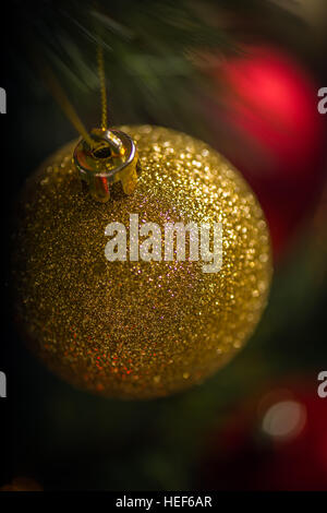 Red and gold baubles stand out against the twinkling lights on a Christmas Tree. - Stock Photo