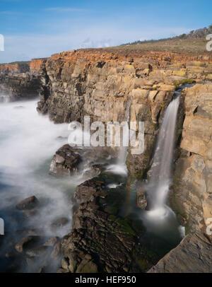 Waterfall onto beach - Stock Photo