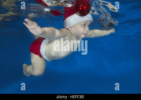 small child learns to swim underwater in the pool - Stock Photo