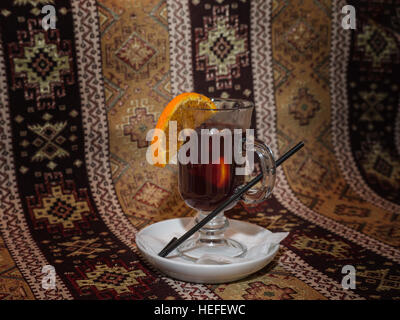 Mulled wine with spices in high glass mug with orange slice on saucer - Stock Photo