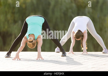woman in yoga straddle position on deck stock photo