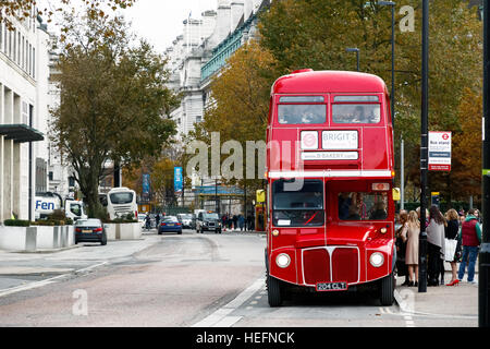 London, UK - November 19, 2016 - People boarding the red bus for an afternoon tea bus tour - Stock Photo