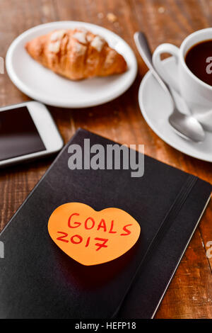 an orange heart-shaped sticky note with the text goals 2017 written in it attached to a black notepad on a rustic - Stock Photo