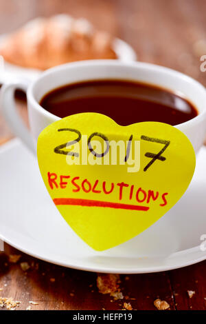 closeup of a yellow heart-shaped sticky note with the text 2017 resolutions written in it attached to a white ceramic - Stock Photo