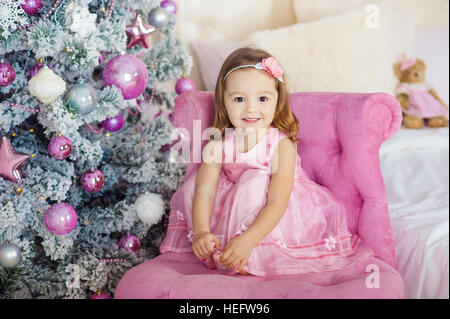 beautiful little girl sits and poses on a chair.   background  festive fir-tree   set of bright fires. Gently smiles. - Stock Photo