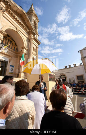 Photo Needs Community outdoor religious festival in Italy, Santi dei Medici.  Priest blessing crowd outside cathedral. - Stock Photo