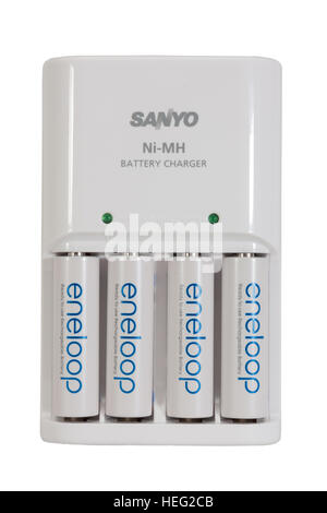 A Sanyo Eneloop battery charger and four NiMH long life rechargeable batteries  isolated on white background - Stock Photo