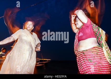 Two Hindu women manifest their devotion through dance during a puja ritual ceremony by the river Ganges in Varanasi, - Stock Photo