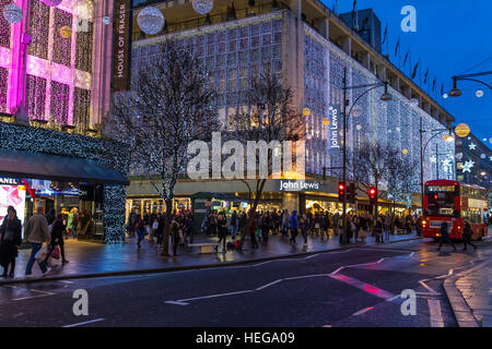 John Lewis Department store on a busy Oxford St bustling with Christmas shoppers at Christmas with The Oxford St - Stock Photo