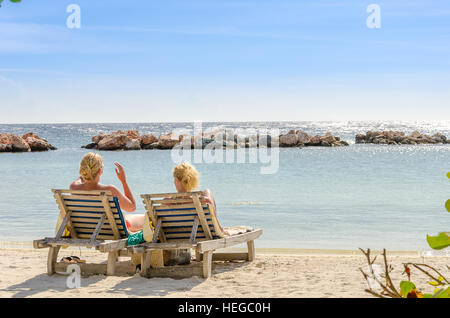 Curacao, Caribbean - September 29, 2012: Two girls got themselves in a front row seats at mambo beach in Curacao. - Stock Photo