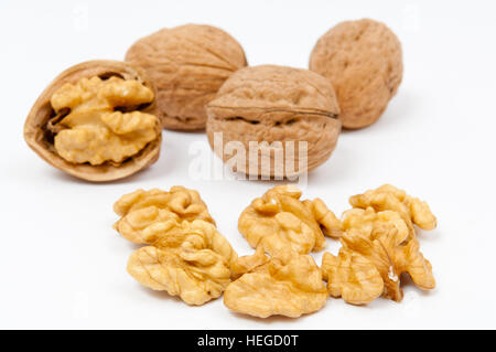 Whole walnuts and walnut kernels on white background - Stock Photo