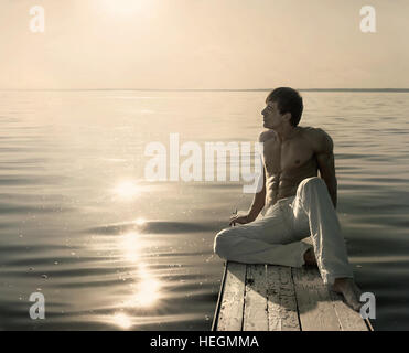 Man sitting on small wooden jetty at summer sunny day - Stock Photo