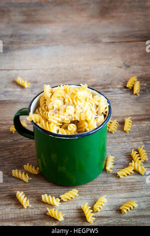 Uncooked raw italian fusilli pasta in rustic metal mug - healthy ingredient for cooking - Stock Photo