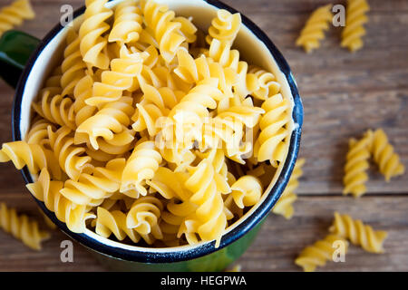 Uncooked raw italian fusilli pasta in metal mug - healthy ingredient for cooking - Stock Photo
