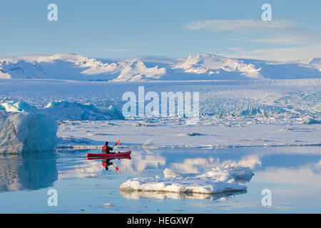 Kayaker in red kayak on the Jökulsárlón glacier lagoon in winter, glacial lake in southeast Iceland - Stock Photo