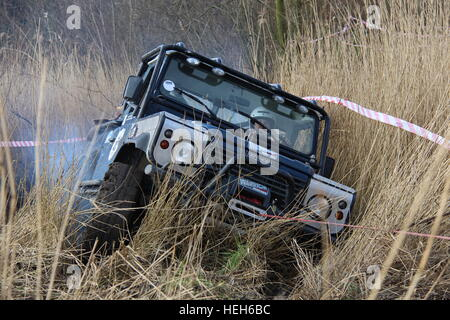 Land Rover Defender 90 winching from muddy swamp during a 4x4 off road challenge in Spaarnwoude, the Netherlands - Stock Photo