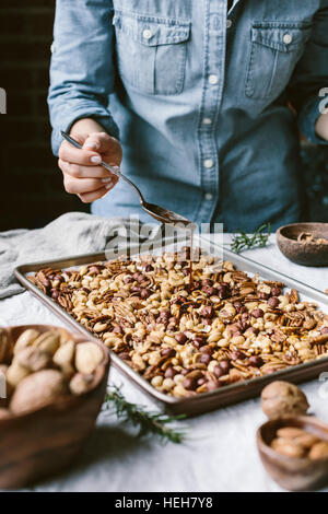 A woman is photographed from the front view as she is drizzling a sheet of mixed nuts with spicy simple syrup. - Stock Photo