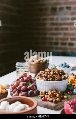 A bowl of spicy candied pecans are photographed from the front view as a part of a cheese and fruit board. - Stock Photo