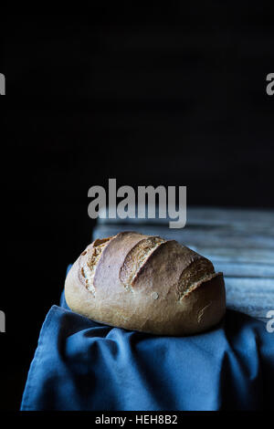 Loaf of bread on wooden table - Stock Photo