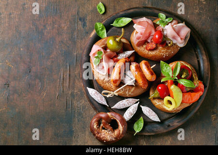Variety of meat snacks fried sausages, wienerwurst, ham, marinated chili peppers served in salted pretzels with - Stock Photo