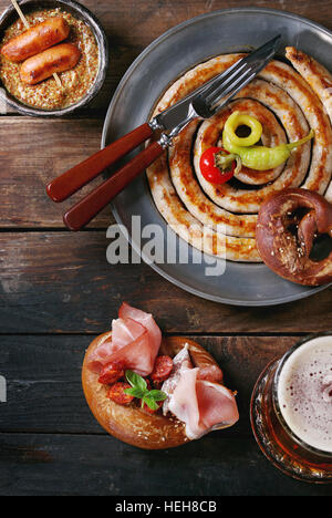 Big spiral fried sausage, meat snacks wienerwurst, ham, marinated chili peppers served in salted pretzels and plate - Stock Photo