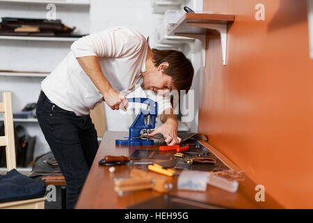 Self-employed tanner using special stapler to put together leather details - Stock Photo
