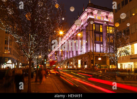 Busy Oxford Street, Christmas shoppers, traffic, and Selfridges. In London, England. - Stock Photo