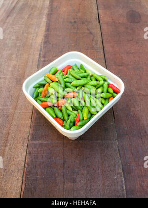 Chillies on the top of the wooden table - Stock Photo