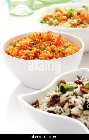 Rice varieties in bowls, Djuvec rice, tomato vegetable rice, long grain rice and wild rice - Stock Photo