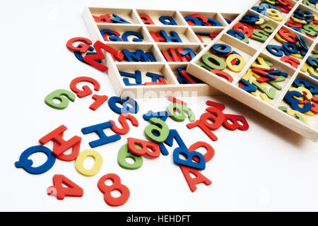 Wooden alphabet, letters and numbers in and beside tray - Stock Photo