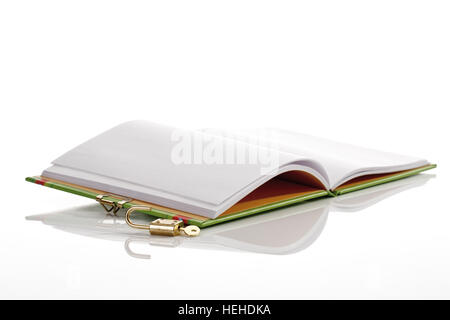 Open lockable diary lying next to key and padlock, lock - Stock Photo