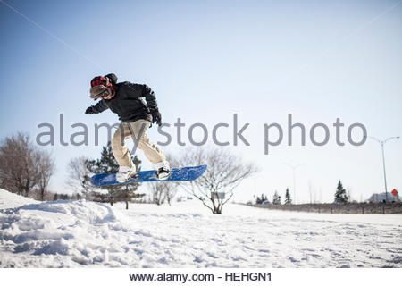 Young man on snowboard performing a stunt in mid air - Stock Photo