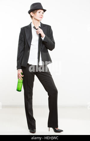 elegant woman in a business suit, holding bottle of alcohol. - Stock Photo