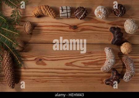 Christmas cookies on wooden table, a table decorated with spruce twig and cone. - Stock Photo