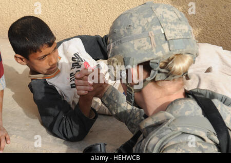 An Iraqi boy challenges U.S. Army Spc. Nicole Willson from Hillsdale, Mich., a medic of Headquarters and Headquarters - Stock Photo