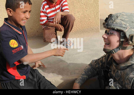 A local Iraqi boy shares a laugh with U.S. Army Spc. Nicole Willson from Hillsdale, Mich., a medic of Headquarters - Stock Photo