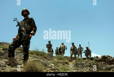 An Afghan national army soldier looks on, as members of 1st Platoon, Alpha Company, 1st Battalion, 32nd Infantry - Stock Photo
