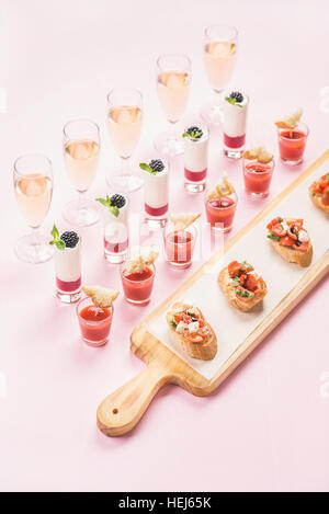 Catering, banquet, party food concept over pastel pink background - Stock Photo