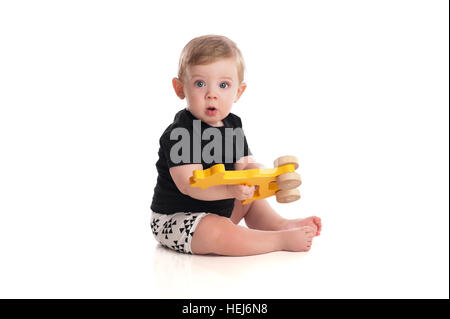 An eight month old baby boy playing with a wooden toy. Isolated on a white background. - Stock Photo