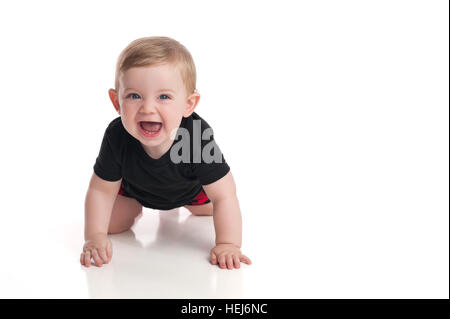 A laughing, eight month old, baby boy crawling toward the camera on a white, seamless background. - Stock Photo