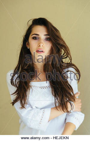 Closeup portrait of depressed crying young woman model with beautiful wavy hair isolated on yellowish background. - Stock Photo