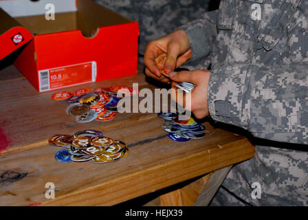 Spc. Ashley Carr of Goldsboro, N.C., sorts and counts pogs to donate to Boy Scouts Troop 223, Dec. 24, from Soldiers - Stock Photo