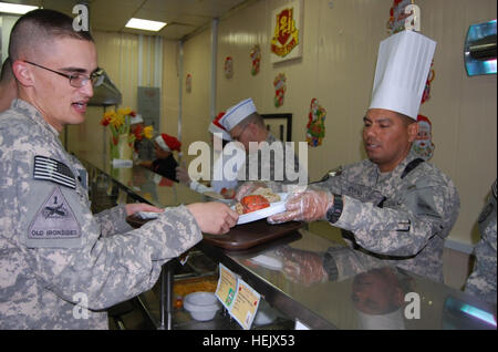 Soldiers of 4th Brigade, 1st Armored Division 'Highlander' enjoy a Christmas Day meal at the Coalition South Dining - Stock Photo