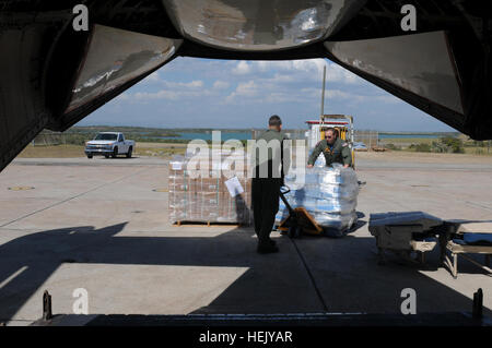 Service members load water and supplies onto an aircraft at U.S. Naval Station Guantanamo Bay en route to Haiti, - Stock Photo