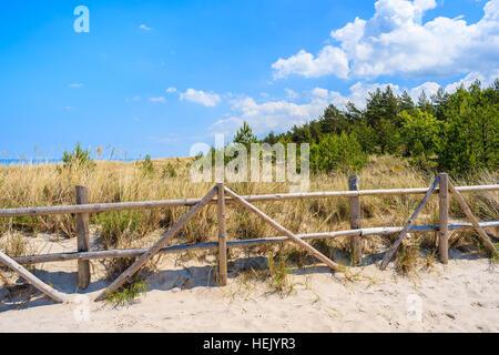 Wooden fence on sand dune on coast of Baltic Sea near Lubiatowo beach, Poland - Stock Photo