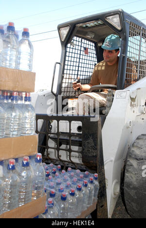 GUANTANAMO BAY, Cuba- Petty Officer 3rd Class Julio Mejia loads pallets of water onto a fork lift outside the Joint - Stock Photo