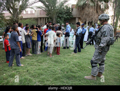 Iraqis from the village of Al Jaffes receive humanitarian assistance from Iraqi police at Sheik Jaffes' home as - Stock Photo