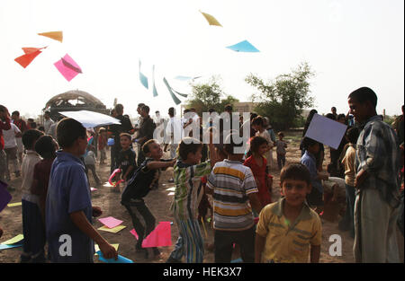 Construction paper rains down like confetti as Iraqis fight to grab a piece after U.S. Soldiers from 3rd Platoon, - Stock Photo