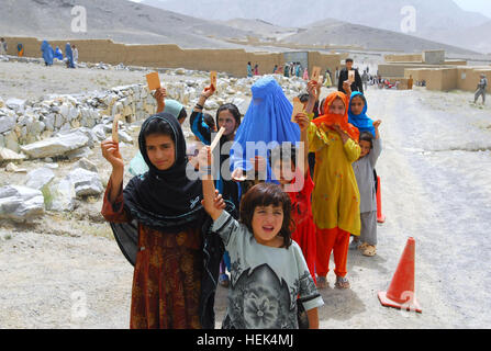Afghan girls in the Naw Abad Village of Kabul Province hold up their tickets at a humanitarian assistance drop, - Stock Photo