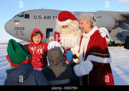 Mr. and Mrs. Santa Claus greet local children after an Alaska Air National Guard C-17 Globemaster military transport - Stock Photo